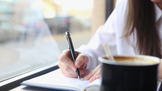 business young woman writing notes closeup. - journalist stock videos & royalty-free footage