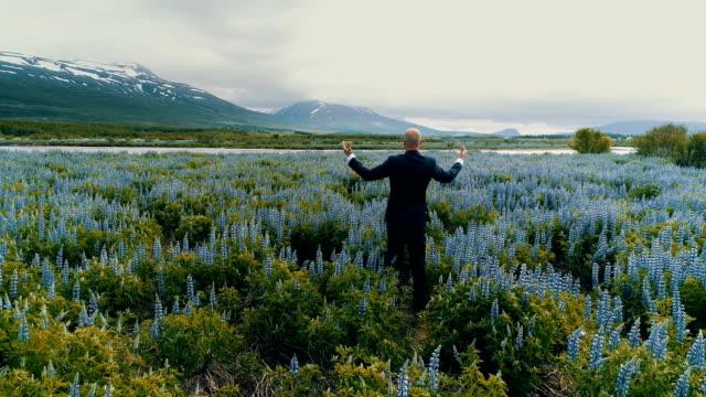businessman admiring meadow full of flowers - sognare ad occhi aperti video stock e b–roll