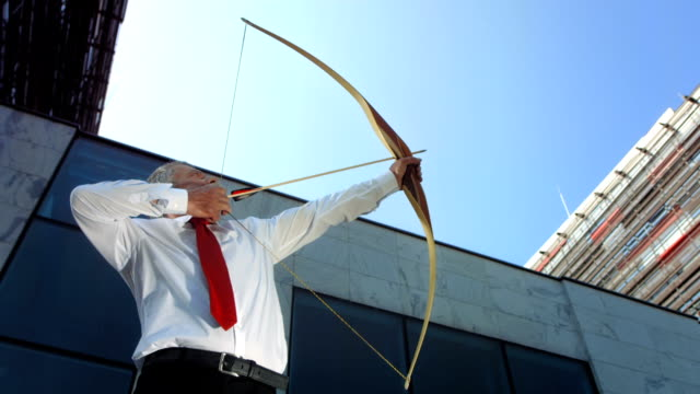 hd dolly: businessman aiming up in the air - longbow stock videos and b-roll footage