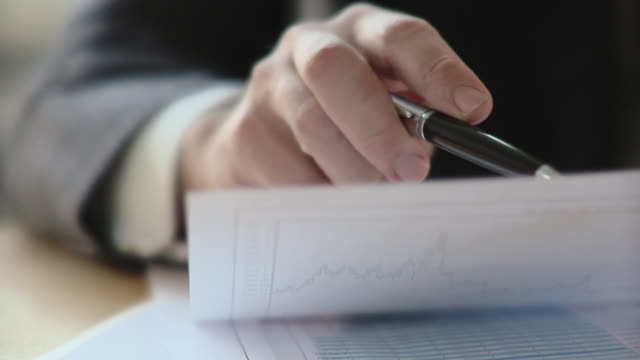ECU, SELECTIVE FOCUS, Businessman analyzing graph, close-up of hand, Berlin, Germany