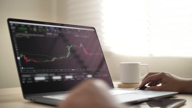uomo d'affari che analizza i dati del mercato azionario su laptop - simbolo video stock e b–roll