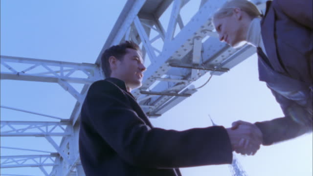 A businessman and a businesswoman shake hands at a meeting near the Eiffel Tower.