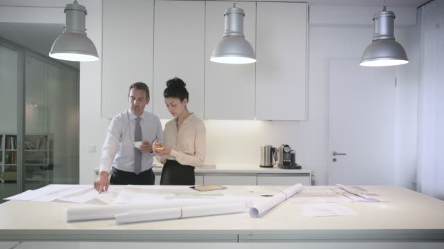 businessman and business woman talk over a break in a creative, stylish office kitchen - ブラウス点の映像素材/bロール
