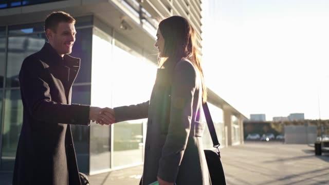 geschäftsmann und geschäftsfrau treffen sich zum ersten mal und händeschütteln - two people stock-videos und b-roll-filmmaterial