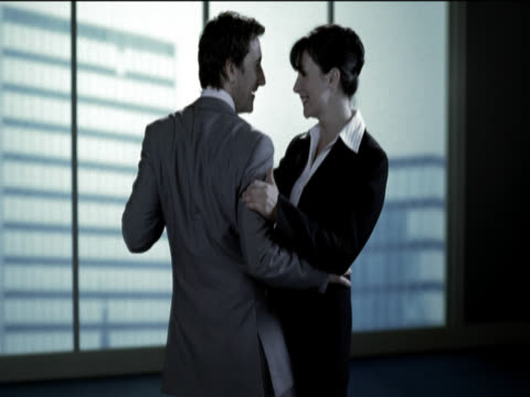 a businessman and businesswoman dancing and flirting together - kompletter anzug stock-videos und b-roll-filmmaterial