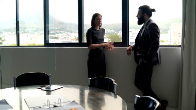 businessman and businesswoman discussing by window - zwei personen stock-videos und b-roll-filmmaterial