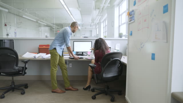 Businessman and businesswoman discussing computer in startup office