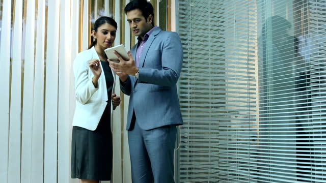 Businessman and businesswoman discussing on digital tablet, Delhi, India