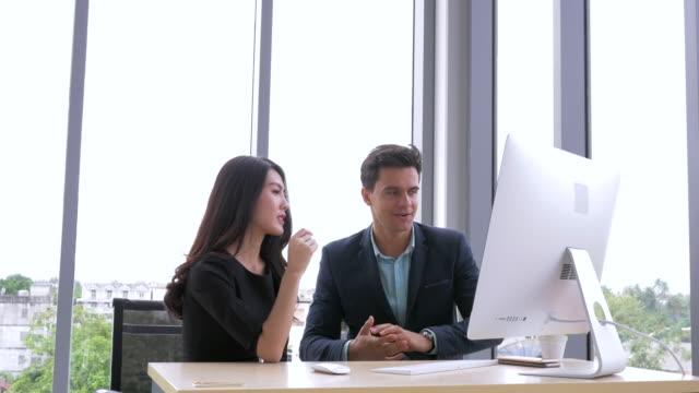 affärsmannen och affärskvinna diskuterar arbete på datorn på kontoret. lagarbete företagets framgångsrika koncept - östasiatiskt ursprung bildbanksvideor och videomaterial från bakom kulisserna