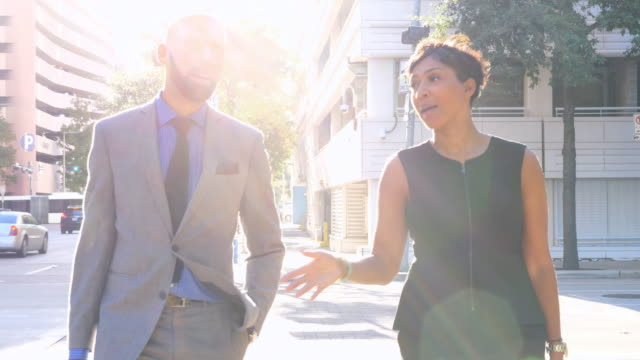 MS Businessman and businesswoman in discussion while walking across city street