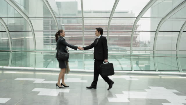 WS Businessman and businesswoman meeting and shaking hands on airport bridge / Toulouse, Haute-Garonne, France