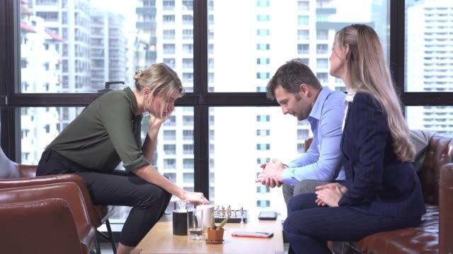 stockvideo's en b-roll-footage met zakenman en zakenvrouw spelen schaken - spelletjesavond