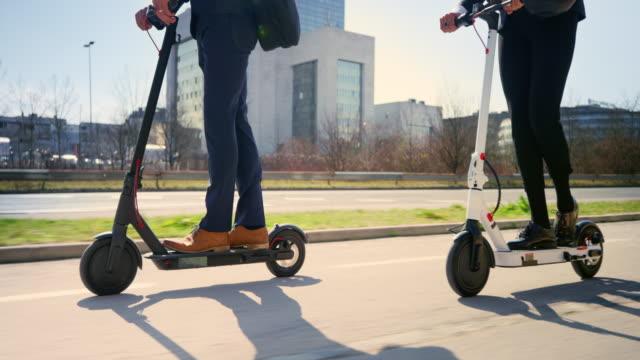 slo mo ts geschäftsmann und geschäftsfrau fahren e-scooter, um an einem sonnigen morgen zu arbeiten - beweglichkeit stock-videos und b-roll-filmmaterial
