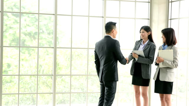 Businessman and businesswoman shaking hands during the meeting, businessman and businesswomen handshake and discussing business plan in digital tablet.