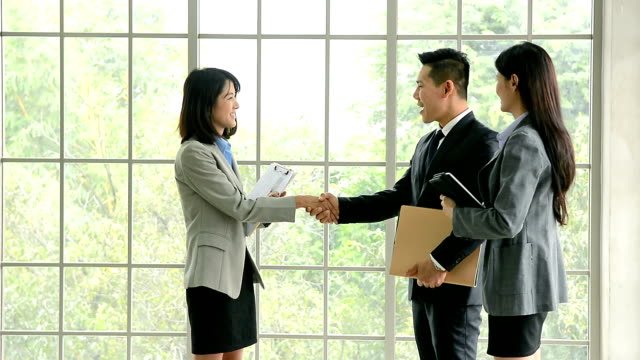 businessman and businesswoman shaking hands during the meeting, businessman and businesswomen have meeting with customer at office - finance and economy stock videos and b-roll footage