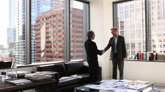 ws businessman and businesswoman shaking hands in corner office - autorität stock-videos und b-roll-filmmaterial