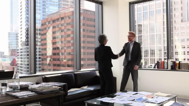 vídeos de stock e filmes b-roll de ws businessman and businesswoman shaking hands in corner office - acordo