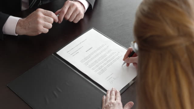 vídeos de stock e filmes b-roll de businessman and businesswoman signing a contract and shaking hands - contrato