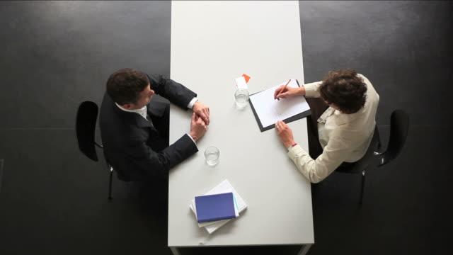 Geschäftsmann und Geschäftsfrau sitzen in Richtung am Schreibtisch. Draufsicht.