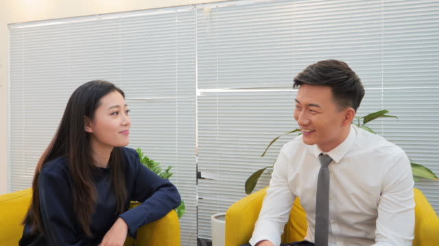MS Businessman and businesswoman sitting and talking in office