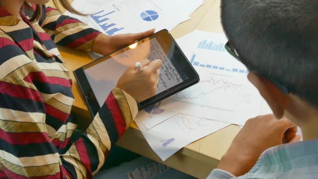 geschäftsmann und geschäftsfrau sitzen am schreibtisch und schauen auf digitales tablet - formelle geschäftskleidung stock-videos und b-roll-filmmaterial