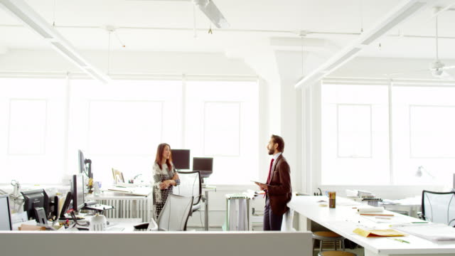MS businessman and businesswoman standing in discussion at office workstation