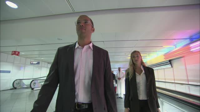 stockvideo's en b-roll-footage met la ms businessman and businesswoman standing on moving walkway in airport / munich, germany - münchen vliegveld