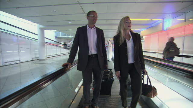 la ws ms businessman and businesswoman talking and standing with luggage on moving walkway in airport / munich, germany - pedestrian walkway stock videos & royalty-free footage