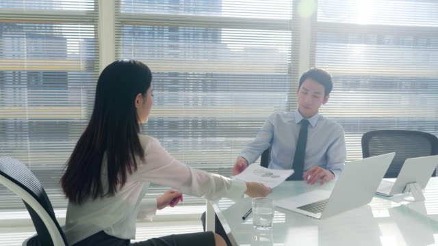 MS Businessman and businesswoman talking at table in office