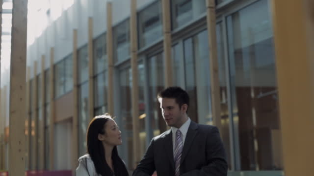 MS TD ZI Businessman and businesswoman talking in front of office building / Vancouver, British Columbia, Canada