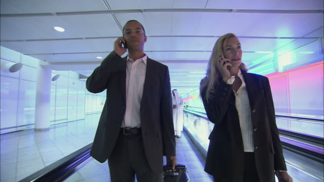 stockvideo's en b-roll-footage met la ms businessman and businesswoman talking on mobile phones and standing with luggage on moving walkway in airport / munich, germany - münchen vliegveld