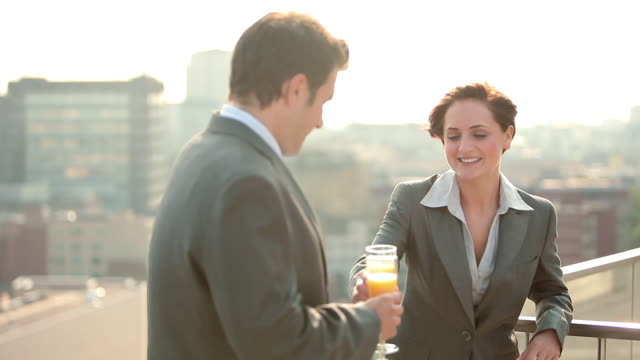 Businessman and businesswoman, toasting and drinking champagne outdoors