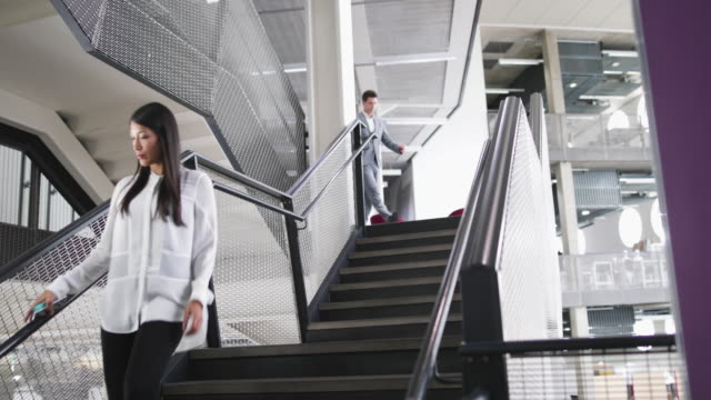 vídeos y material grabado en eventos de stock de businessman and businesswoman walking down stairs in an office - steps and staircases