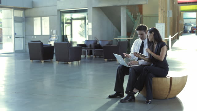 ws ds businessman and businesswoman working in office lobby / vancouver, british columbia, canada - eingangshalle gebäudeteil stock-videos und b-roll-filmmaterial