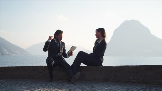 geschäftsmann und geschäftsfrau arbeiten im freien an steinmauer mit blick auf den see - elegante kleidung stock-videos und b-roll-filmmaterial