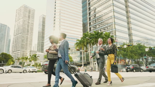 businessman and colleagues walking on road in city at downtown miami - formal stock videos & royalty-free footage