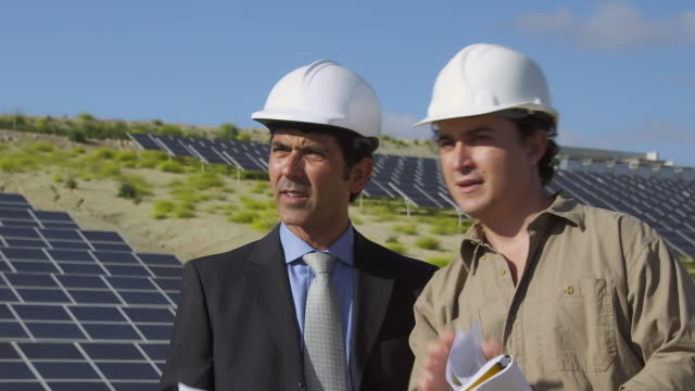 ms businessman and engineer discussing plans in front of photovoltaic (solar) plant / malaga, spain - completo da uomo video stock e b–roll
