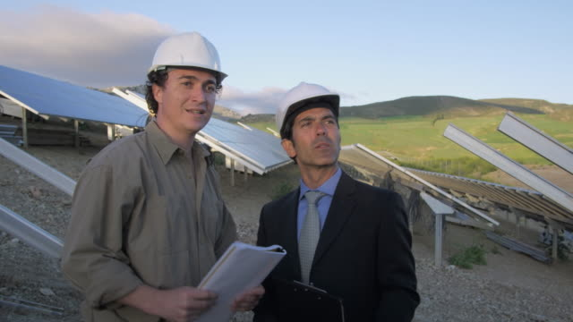 cu ms businessman and engineer in photovoltaic (solar) plant, discussing project / malaga, spain - completo da uomo video stock e b–roll