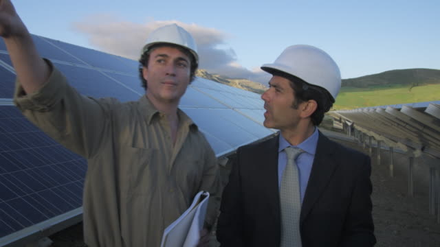 ms businessman and engineer walking through photovoltaic (solar) plant, discussing project / malaga, spain - completo da uomo video stock e b–roll