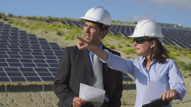 stockvideo's en b-roll-footage met ms zi businessman and female engineer discussing plans and shaking hands in front of photovoltaic (solar) plant / malaga, spain - compleet pak