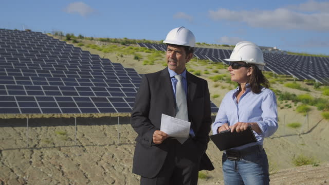 ms businessman and female engineer discussing plans and shaking hands in front of photovoltaic (solar) plant / malaga, spain - completo da uomo video stock e b–roll