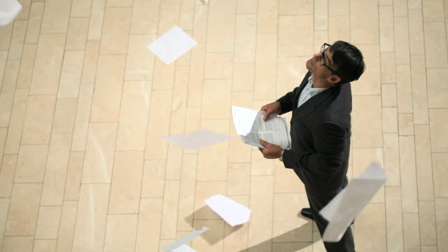 Businessman and papers falling from above