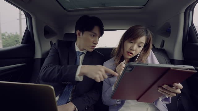 businessman and secretary using electronic organizer while travelling in car - electronic organizer stock videos & royalty-free footage