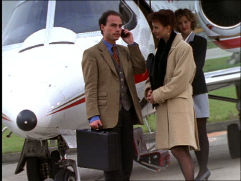 businessman and woman by jet / man on cellular phone - 1997 stock-videos und b-roll-filmmaterial