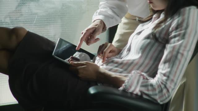 MS TU Businessman and woman discussing, using digital tablet / Brooklyn, New York, USA