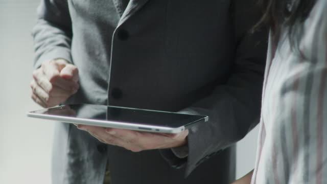 CU TU Businessman and woman hands using digital tablet / Brooklyn, New York, USA