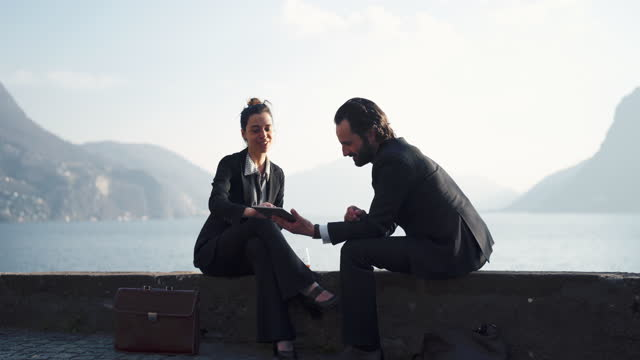 businessman and woman in suits sitting remote working on tablet view of lake and mountains behind - businessman stock videos & royalty-free footage