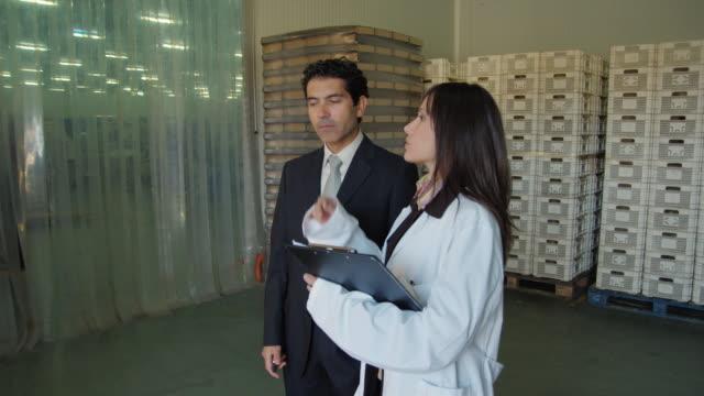 vidéos et rushes de ms ds businessman and woman in white coat talking in loading bay of food processing plant / algarrobo, malaga, spain - deux personnes