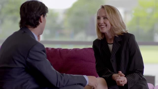 vídeos y material grabado en eventos de stock de mls ds  businessman and woman talking on sofa - vestimenta de negocios formal