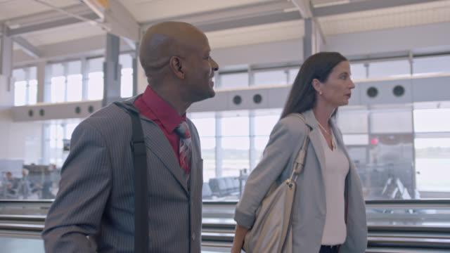vidéos et rushes de businessman and woman walk and talk as they travel down moving walkway in airport terminal. - collègue de bureau